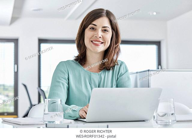 Portrait of smiling young businesswoman using laptop at desk in office