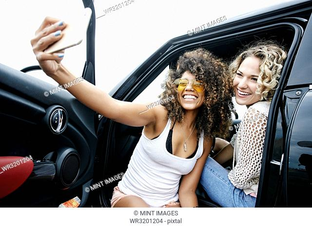 Portrait of two smiling young women with blond and brown curly hair sitting in car, taking selfie with mobile phone