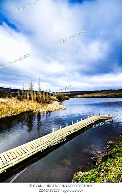 Pier landscape captured in vertical format with cloud sky copy space of a angled fishing pier in Ouse, Tasmania, Australia