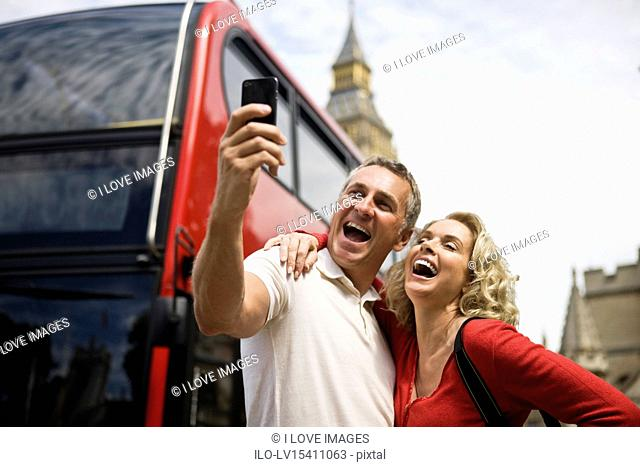 A middle-aged couple standing at Parliament Square, taking a photograph, laughing