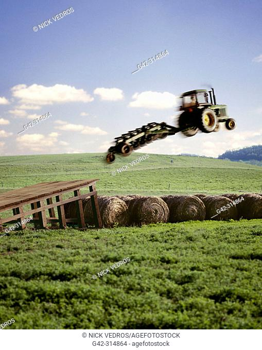 Tractor with plow jumping hay bales