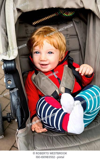Toddler sitting in pushchair, smiling