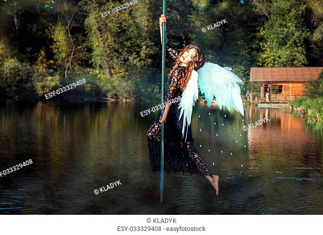 Girl with angel wings dancing on the pole. Pole dance in the middle of the river