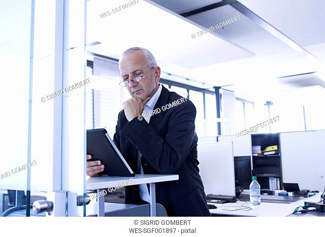 Businessman in open space office using digital tablet