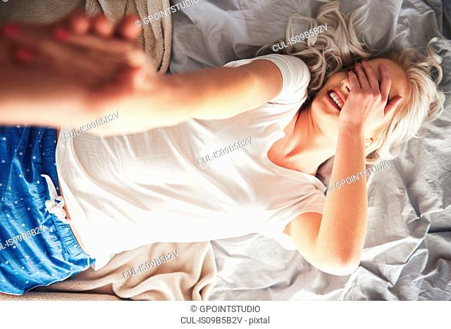 Woman lying on bed, man pulling her off bed, elevated view