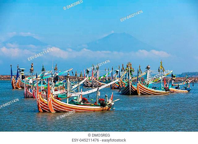 Traditional old wooden fishing boats in Bugis style mooring in old fishers port on Bali island near Perancak village. Popular place to visit in Jembrana regency