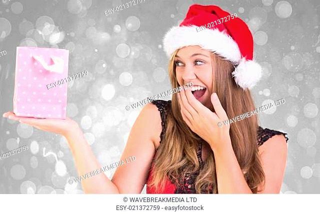 Composite image of festive blonde holding a gift bag