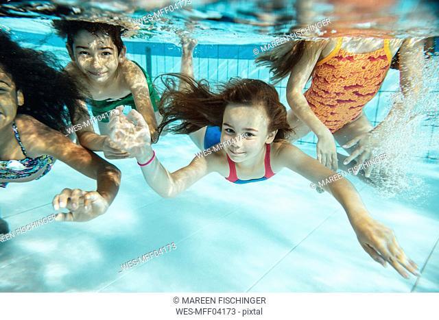 Portrait of happy children swimming under water in swimming pool