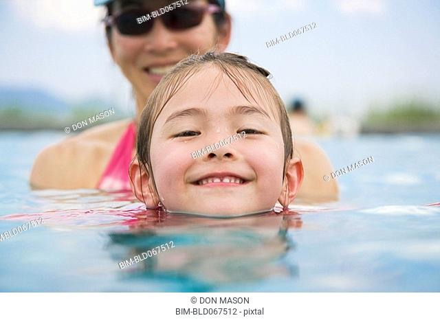Asian girl and mother in swimming pool