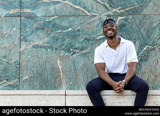 Cheerful young man in headscarf sitting against patterned wall
