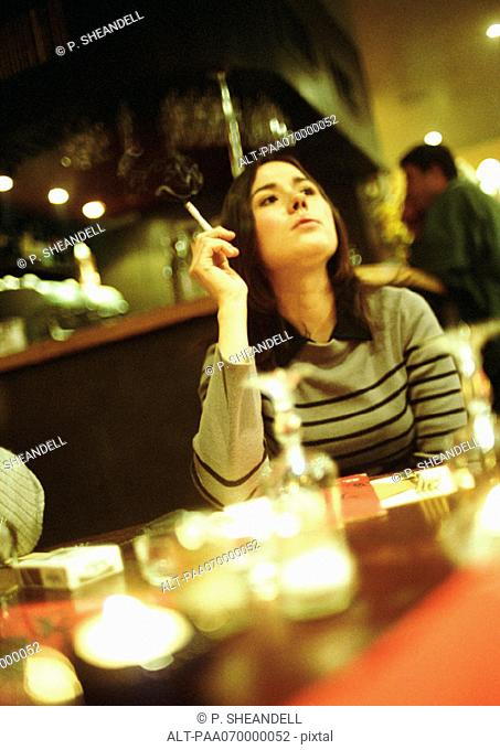 Young woman sitting in cafe, smoking a cigarette