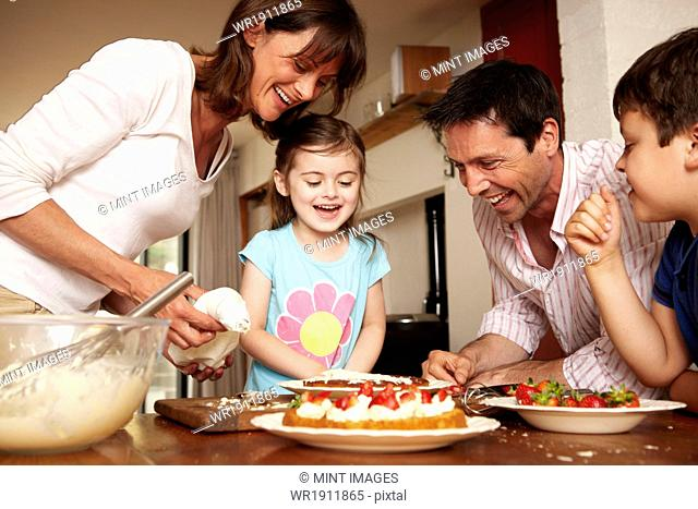 A family, two parents and two children in the kitchen icing a cake with fruit and cream