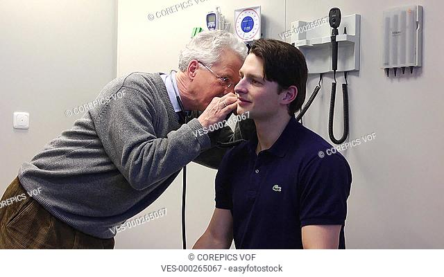 General practitioner using an ocular to examine a patient's inner ear