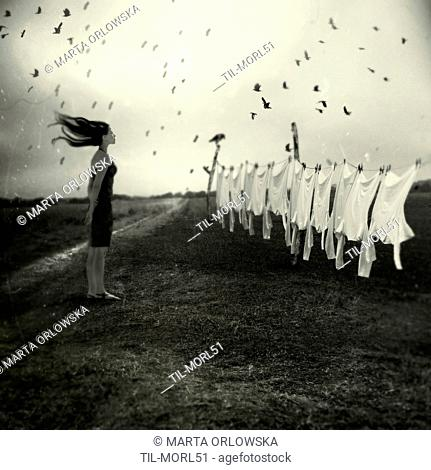 Conceptual image of a young woman standing alone in fields looking at washing hanging on a line with birds flying