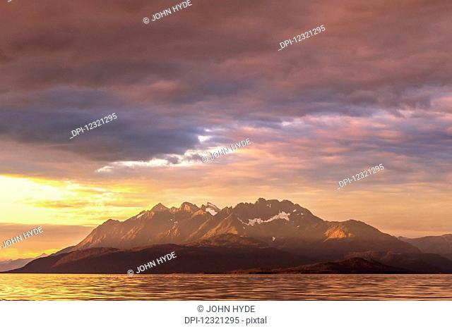A summer sunset colours the sky in Lynn Canal, Inside Passage, near Juneau, with a view of Lions Head Mountain; Alaska, United States of America