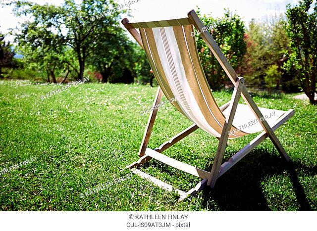 Empty deckchair in sunlit garden