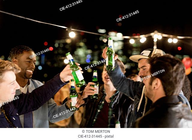 Young men drinking beer and dancing at rooftop party