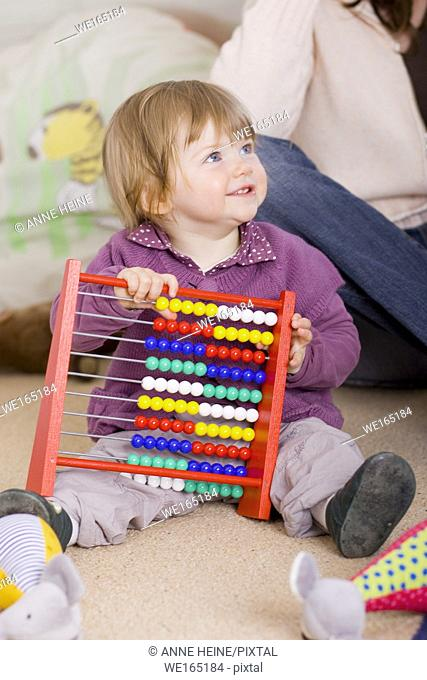 girl one year old sitting on floor learning with slide rule