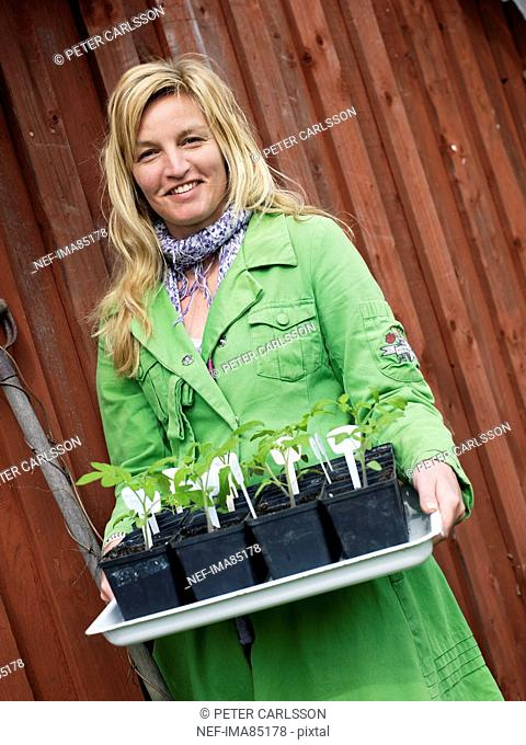 Portrait of young woman holding tray with seedlings