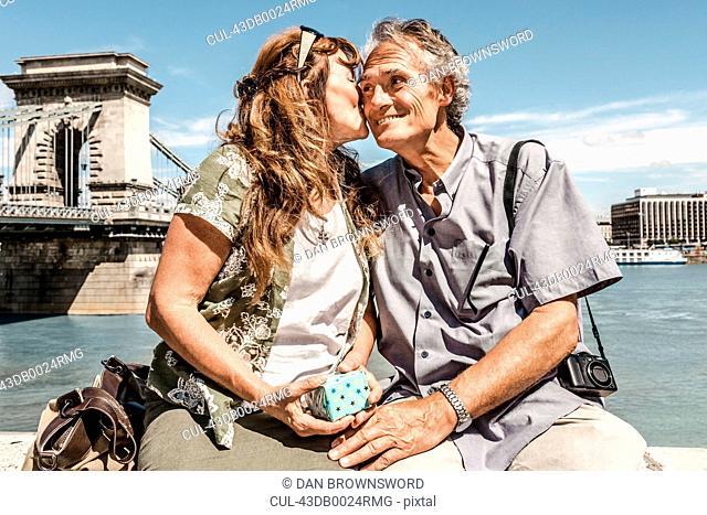Older couple kissing on bridge