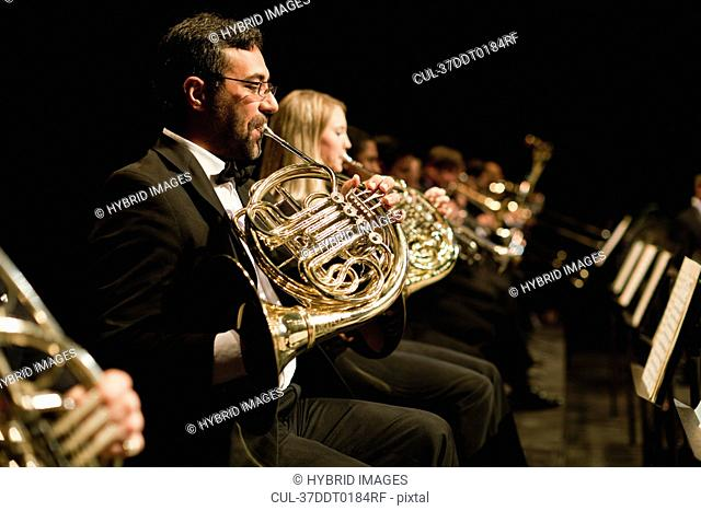 French horn players in orchestra