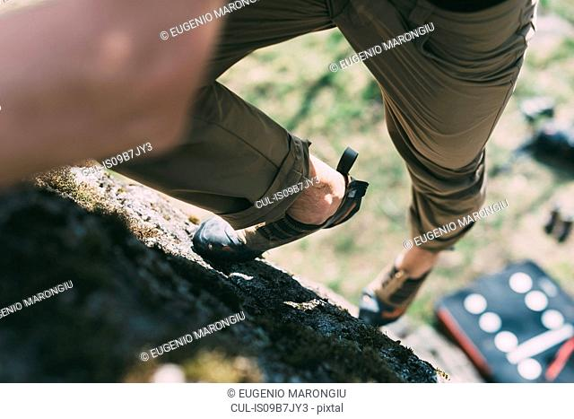 Waist down view of male boulderer climbing up boulder, Lombardy, Italy