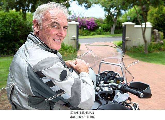 Portrait of happy senior man on motorcycle in driveway