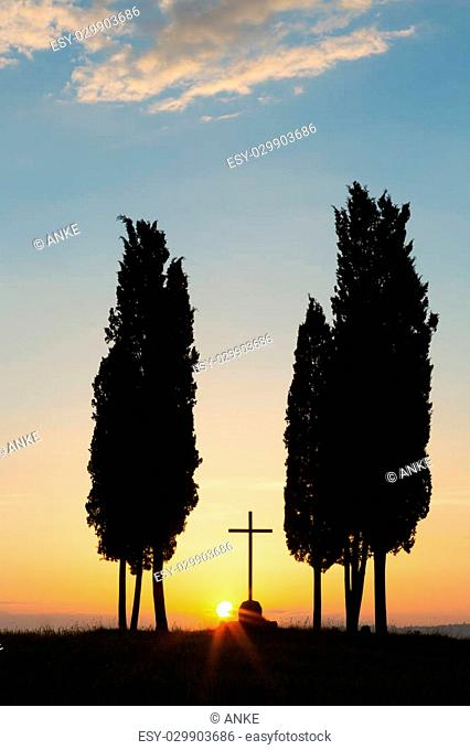 Cypress trees and lonely cross on a hill in Tuscany near Pienza Italy
