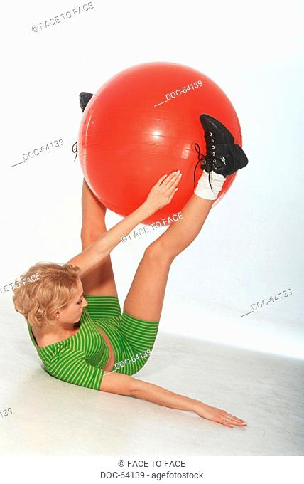 Young adult woman does doing sports practices - a red seat ball between the legs hold