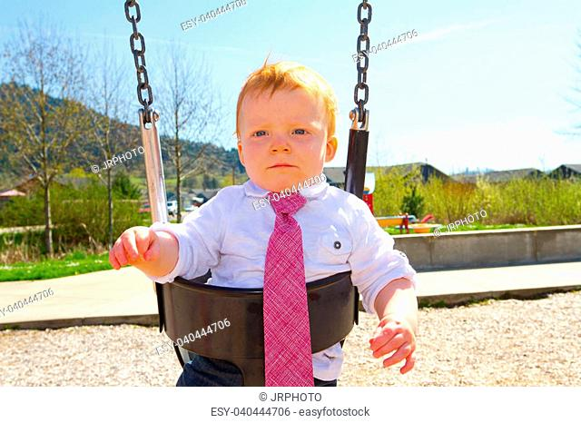 A baby boy plays on a swing set at the park wearing nice clothing