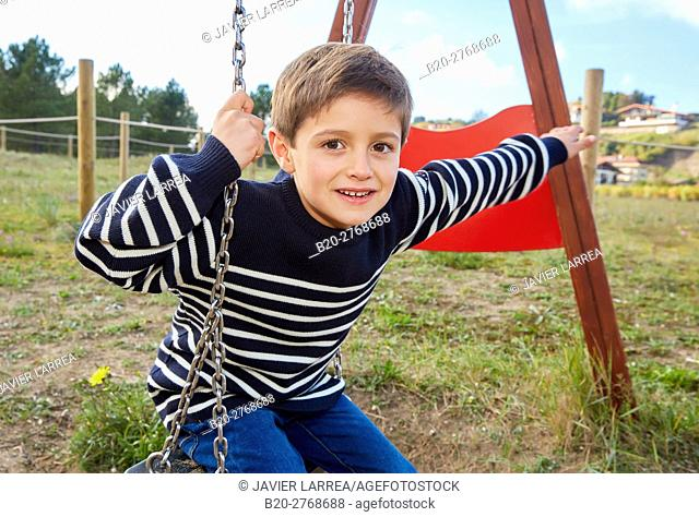Swing, Boy playing in a playground, Zumaia, Gipuzkoa, Basque Country, Spain