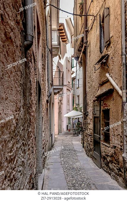 narrow bending alley in historical touristic village, shot on bright summer day at Orta San Giulio, Novara, Cusio, Italy