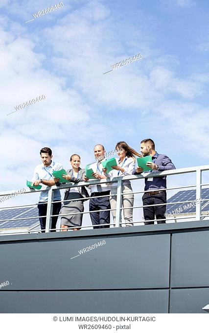 Business people in front of solar paneling holding papers