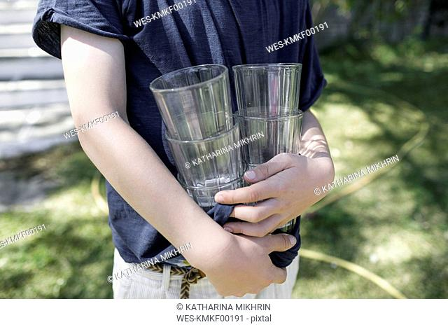 Boy standing in garden holding empty glasses, partial view
