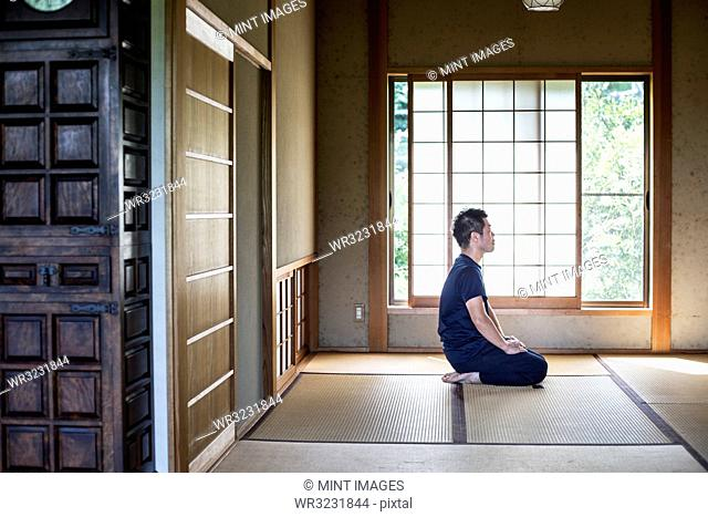 Japanese man kneeling on tatami mat in traditional Japanese house
