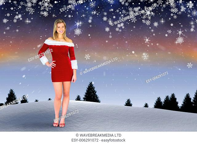Pretty girl smiling in santa outfit against snow falling on fir tree forest