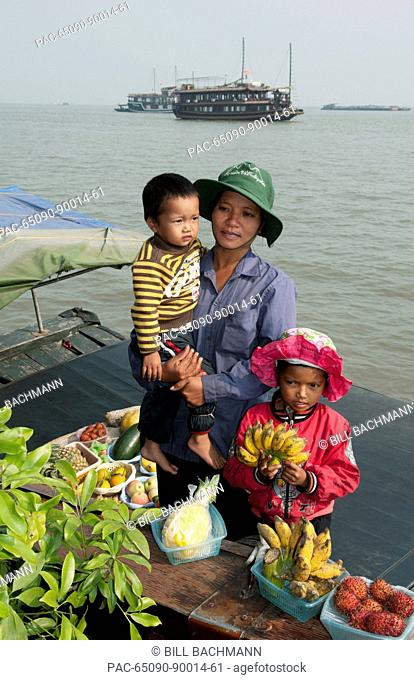 South East Asia, Vietnam, Ha Long Bay, Vietnamese woman and her children sell fresh fruit in harbor