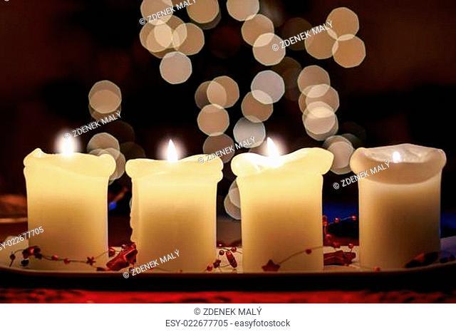Burning candle with christmas tree bokeh