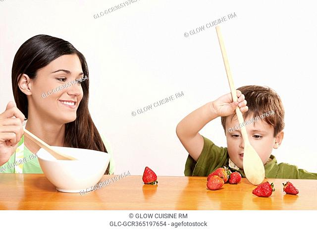 Boy playing with strawberries at a dining table