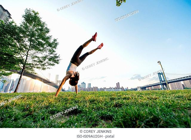 Young woman doing handstand in park, New York, USA