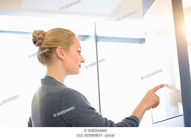 Young businesswoman in office pointing at board