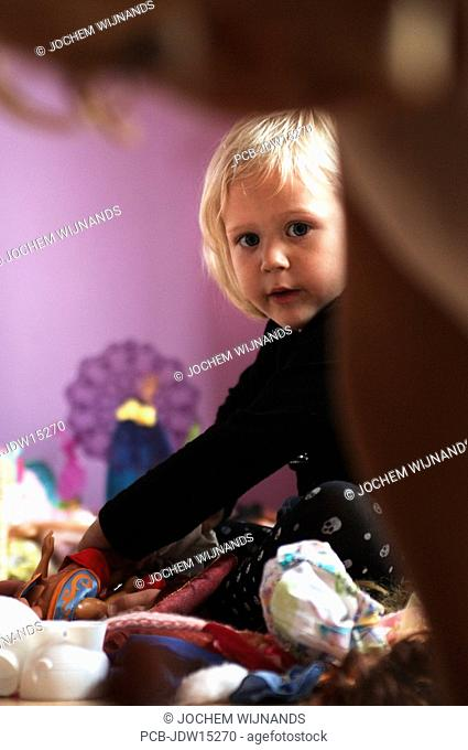 Three year old girl playing in her room