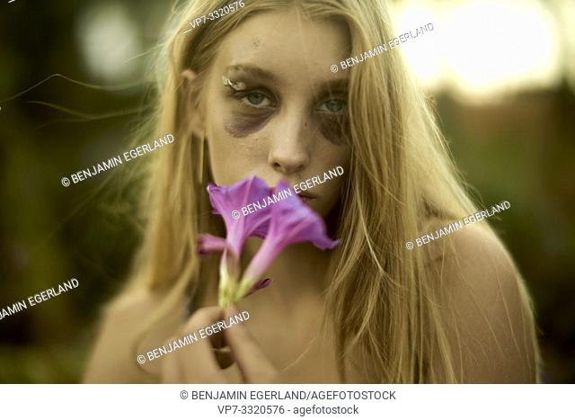 young defaced teenage woman with black eye holding pink flower, scars