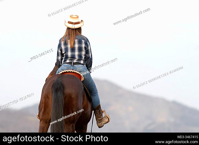 Back view of a young cowgirl on her horse