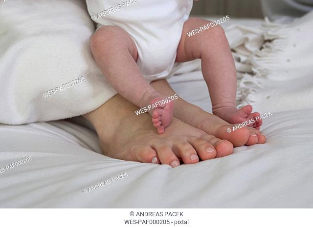 Feets of father and his newborn baby girl