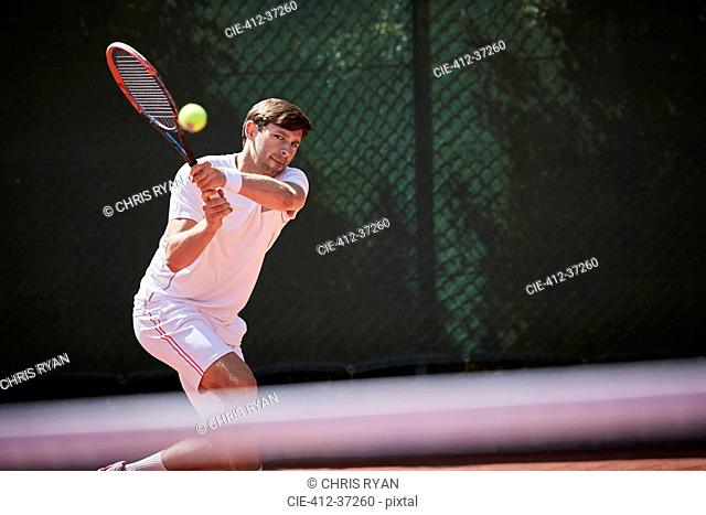 Young male tennis player playing tennis, hitting the ball on sunny tennis court