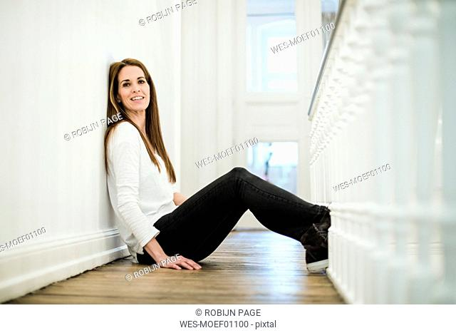 Portrait of smiling woman at home sitting on the floor