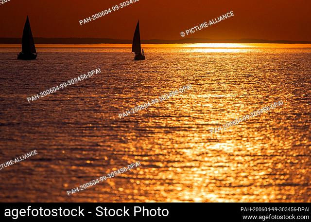 02 June 2020, Mecklenburg-Western Pomerania, Timmendorf (poel): A sailing boat crosses the Baltic Sea at sunset to the small harbour of Timmendorf on the island...