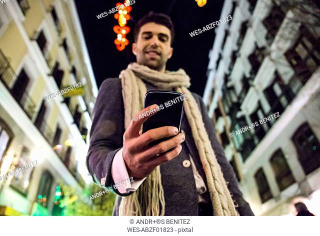 Man using his cell phone in the city at night