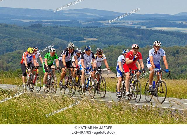 A group of cyclists cycling up a hill with Frankenberger Land behind, Frankenau, Hesse, Germany, Europe